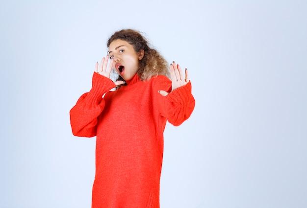 Женщина в красной рубашке останавливает и предотвращает что-то.