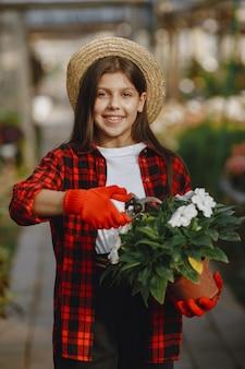 Женщина в красной рубашке. рабочий с цветочными горшками. дочь с растениями