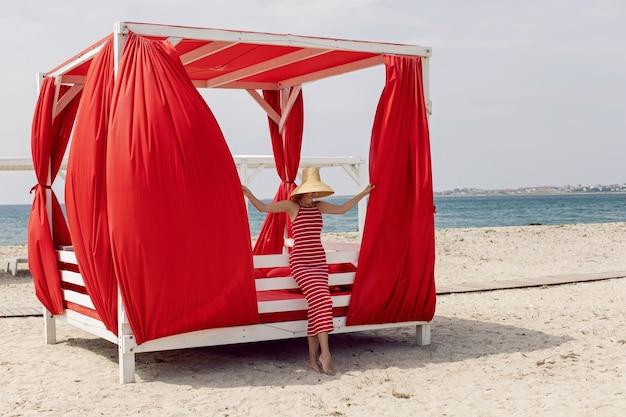 Женщина в красном полосатом платье стоит рядом с шезлонгом на песчаном пляже