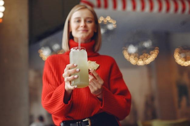 赤いセーターを着た女性。女性はカクテルを飲みます。