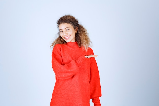 さまざまな側面を指している赤いスウェットシャツの女性。