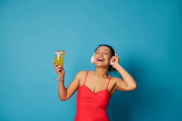 青い背景に彼女の手でカクテルを保持している赤い水着とヘッドフォンの女性
