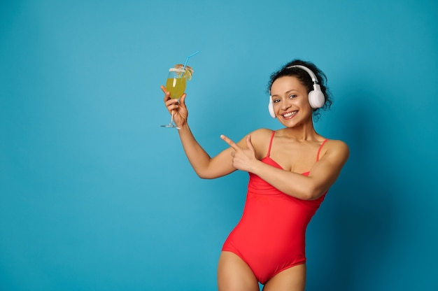 青い背景に彼女の手でカクテルを指している赤い水着とヘッドフォンの女性
