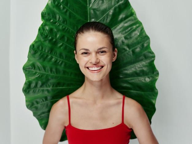 赤い水着の女性笑顔緑の葉エキゾチックな明るい背景