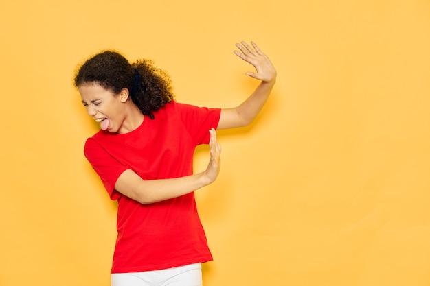 Женщина в красной футболке с отвращением смотрит в сторону, высунув язык