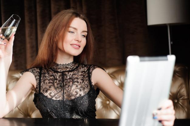 Женщина в ресторане расслабляющий с бокалом шампанского и планшетных пк.