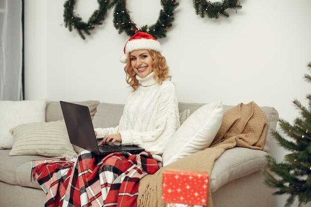 방에있는 여자. 하얀 스웨터에 금발. 노트북과 레이디.