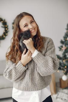 部屋の女性。灰色のセーターを着た人。小さな子猫を持つ女性。
