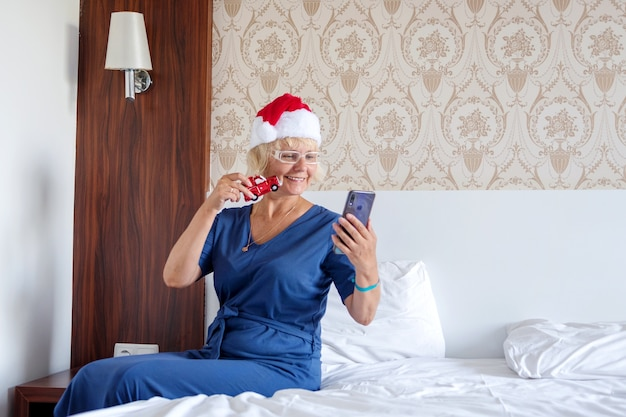 ベッドの上にスマートフォンを持つサンタクロースの帽子の女性