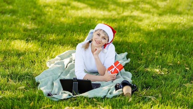 산타 모자를 쓴 여성이 비디오 링크를 통해 가족에게 전화를 겁니다. 온라인 인사말