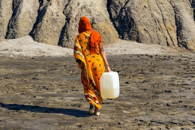 사리와 히잡을 쓴 여성이 생명이 없는 사막 계곡 위로 물이 든 플라스틱 제리칸을 나르고 있다