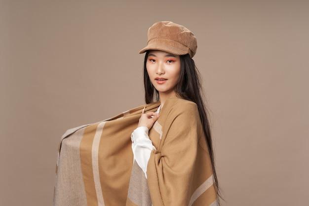 彼女の頭のブルネットのアジアの外観にシャツとベージュのケープの帽子をかぶった女性