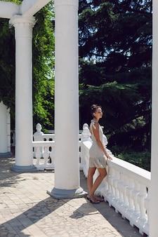 夏のクリミア半島の自然の中で柵と白い柱の隣に立っている短いドレスとサングラスの女性