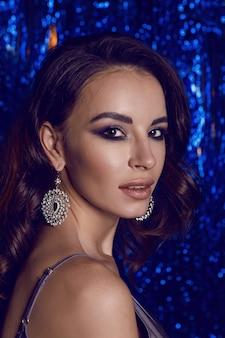 Женщина в коротком платье стоит в клубе на праздник нового года в ювелирных синих ленточках
