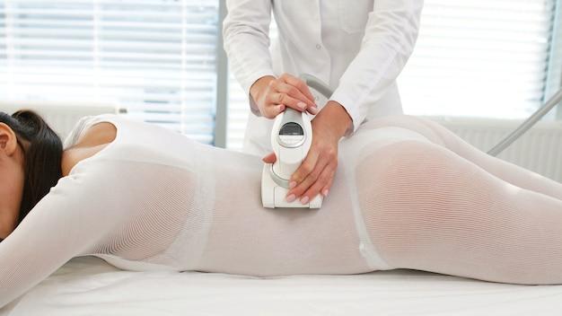 Женщина в специальном белом костюме получает аппаратный антицеллюлитный lpg-массаж