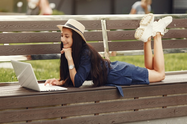 Женщина в весеннем городе. дама с ноутбуком. девушка сидит на скамейке.