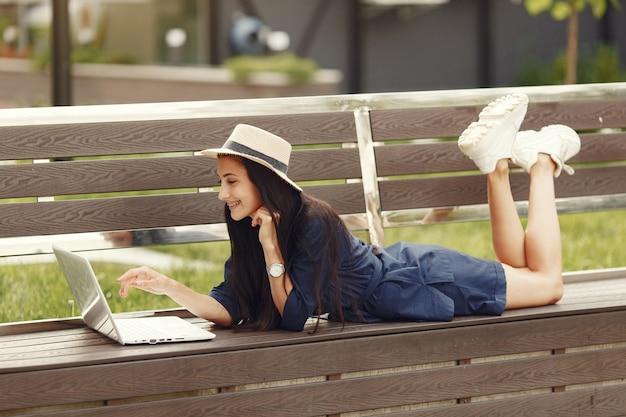 春の街の女性。ノートパソコンを持つ女性。ベンチに座っている女の子。