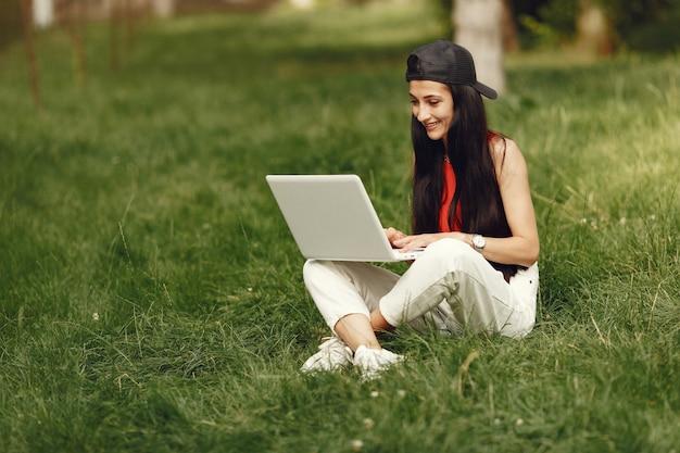 春の街の女性。ノートパソコンを持つ女性。草の上に座っている女の子。