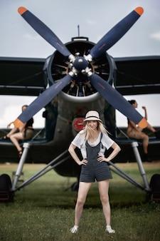 프로펠러가있는 비행기를 배경으로 포즈를 취하는 배경에 밀짚 모자에있는 여자
