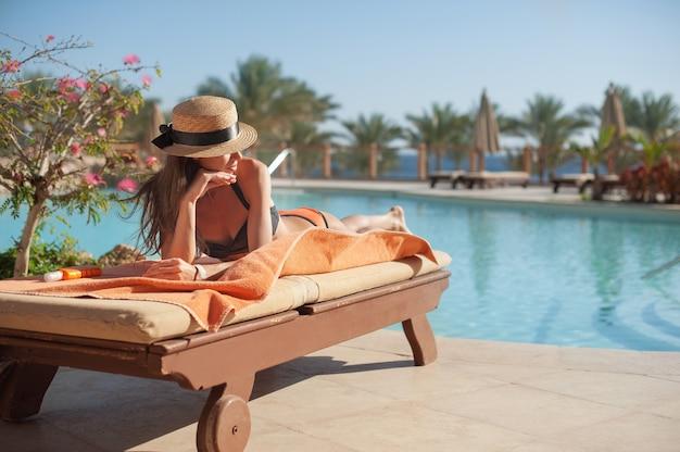 Женщина в соломенной шляпе отдыхает на кушетке возле роскошного летнего отеля с бассейном