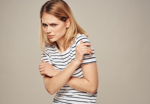 베이지 색 바탕에 손으로 자신을 포옹하는 스트라이프 티셔츠에 여자. 고품질 사진