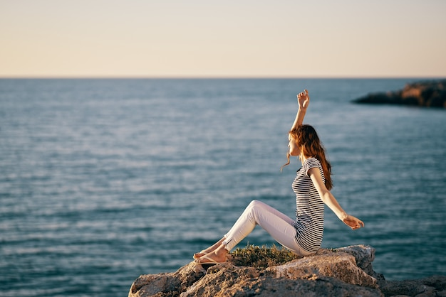 Женщина в полосатой футболке подняла руки вверх у моря