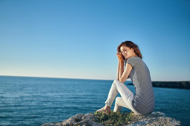 여름에는 줄무늬 티셔츠와 흰 바지를 입은 여성이 산속의 바다 근처 돌 위에 있습니다.