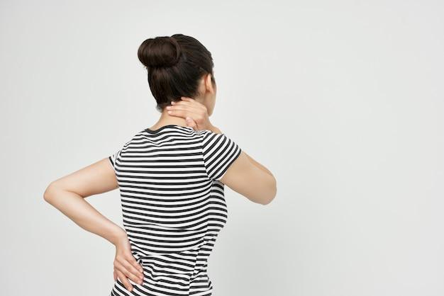 首の健康問題の縞模様のtシャツの痛みの女性