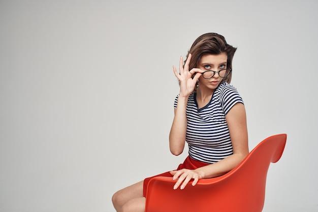 赤い椅子に座っている縞模様のtシャツの女性モダンなスタイルの髪型