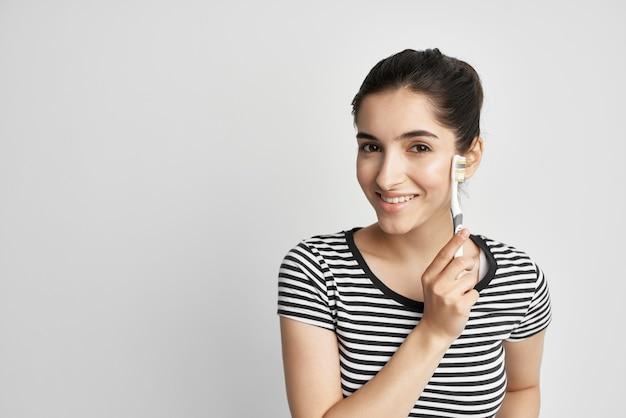 手に明るい背景の縞模様のtシャツの歯ブラシの女性 Premium写真
