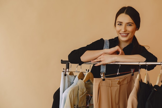 Женщина в студии с большим количеством одежды