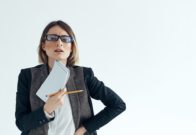 シャツとジャケットの明るい背景のトリミングされたビューにドキュメントを持つスーツの女性。高品質の写真
