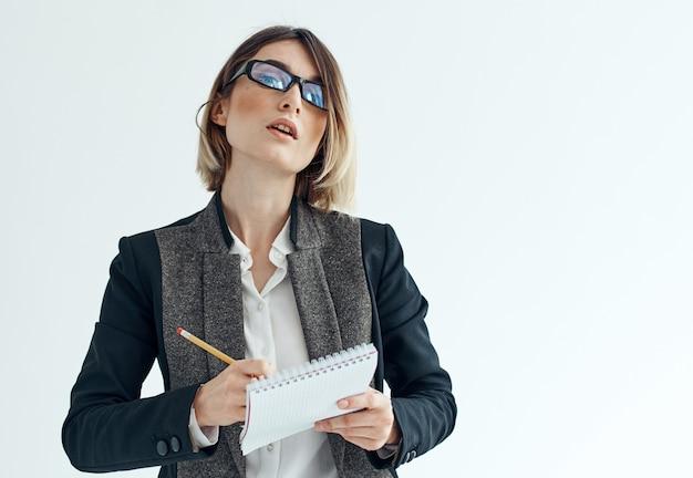 Женщина в костюме с документами на легком обрезанном пиджаке с рубашкой