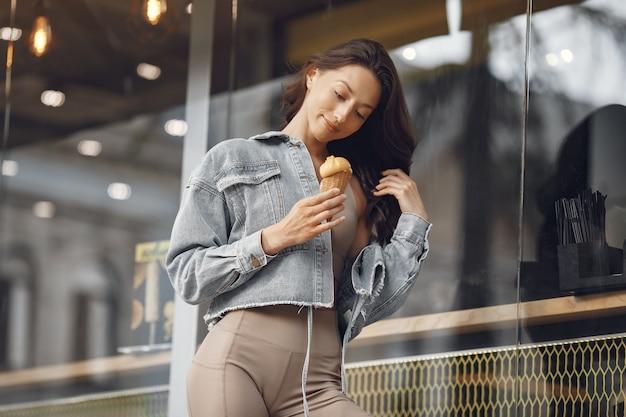 夏の街の女性。アイスクリームの女性。建物のそばのブルネット。