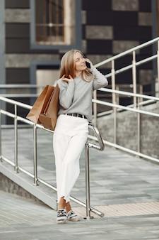 Женщина в летнем городе. дама с мобильным телефоном. женщина в сером свитере.