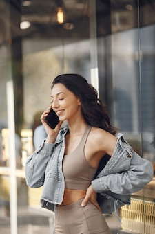 夏の街の女性。電話を持つ女性。建物のそばのブルネット。