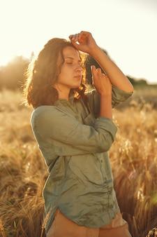 여름 필드에 여자입니다. 녹색 셔츠에 갈색 머리. 일몰 배경에 소녀입니다.