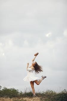 夏の畑の女性。白いドレスのブルネット。音楽スピーカーを持つ少女。