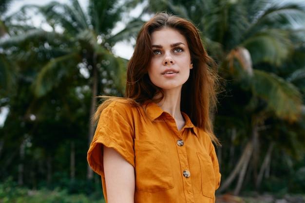 ヤシの木のエキゾチックな熱帯地方の緑の葉の近くのサンドレスの女性