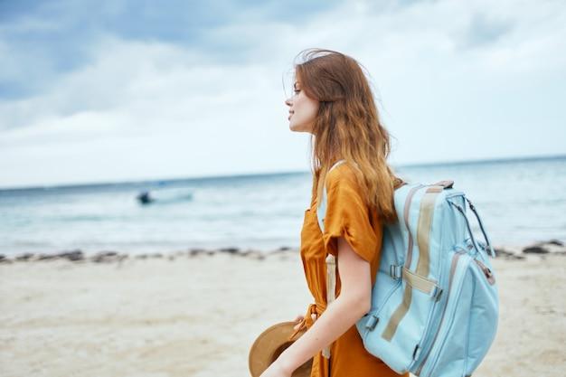 背中にバックパックを背負ってサンドレスを着た女性が海の近くのビーチを歩く