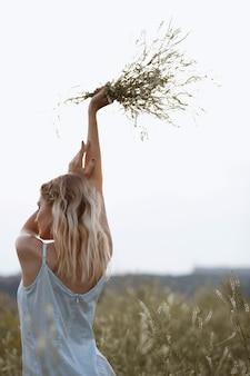 Женщина в сарафане с букетом полевых трав на прогулке