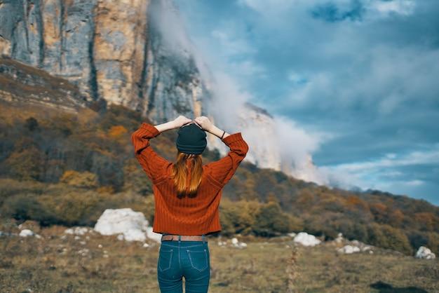 セーターと腕を上げたジーンズの女性は、自然の風景の山を旅します