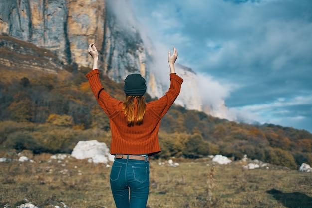 セーターとジーンズを着た女性が腕を上げ、自然の風景の中を山の中を旅する