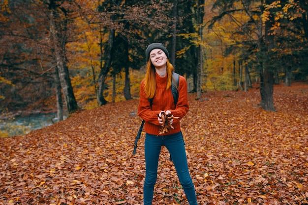 Женщина в законе джинсов шляпы свитера на спине и природе