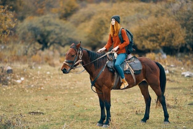 自然の中で馬に乗ってセーターを着た女性