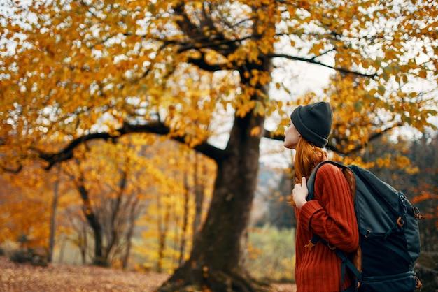 セーターを着た女性が秋の自然の風景の新鮮な空気モデルのバックパックで公園を歩く
