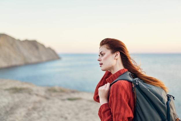 山の海の近くで背中にバックパックを背負ったセーターの女性笑顔楽しいモデル