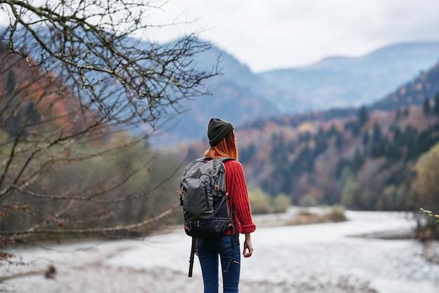 バックパックを背負ったセーターを着た女性が山の川沿いを歩く