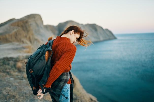 バックパックを背負ったセーターを着た女性が、海の近くの山の自然の中を歩く
