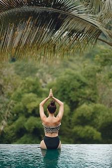 Женщина в бассейне с видом на джунгли